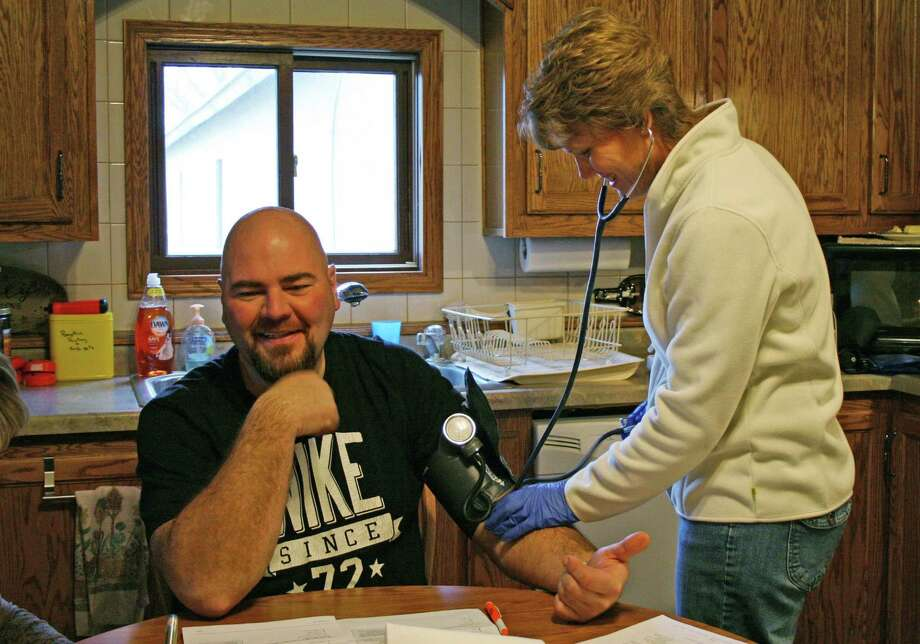 Providing basic preventive care, Rural Health Initiative nurse Dawn Dingeldein checks dairy farmer Jay Vomastic's blood pressure in his home in Shawano County, Wis. Photo: M.L. Johnson / Associated Press / AP