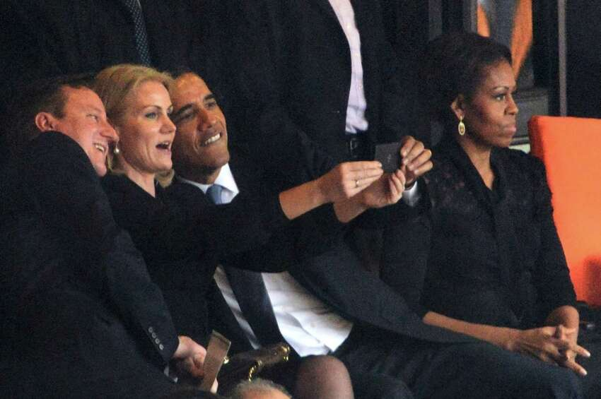 President Barack Obama (right) and British Prime Minister David Cameron pose for a selfie picture with Denmark's Prime Minister Helle Thorning Schmidt (center) next to first lady Michelle Obama  during the memorial service of South African former president Nelson Mandela.