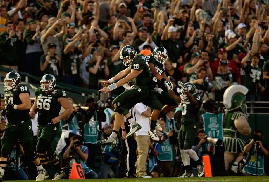 Quarterback Connor Cook #18 and running back R.J. Shelton #12 of the Michigan State Spartans celebrate after a touchdown against the Stanford Cardinal during the 100th Rose Bowl Game. Photo: Harry How, Getty Images