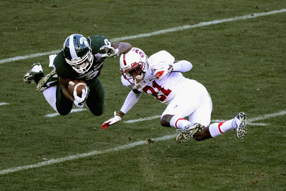 Wide receiver Macgarrett Kings Jr. #3 of the Michigan State Spartans makes a catch as defensive back Ronnie Harris #21 of the Stanford Cardinal defends during the 100th Rose Bowl Game. Photo: Jonathan Moore, Getty Images