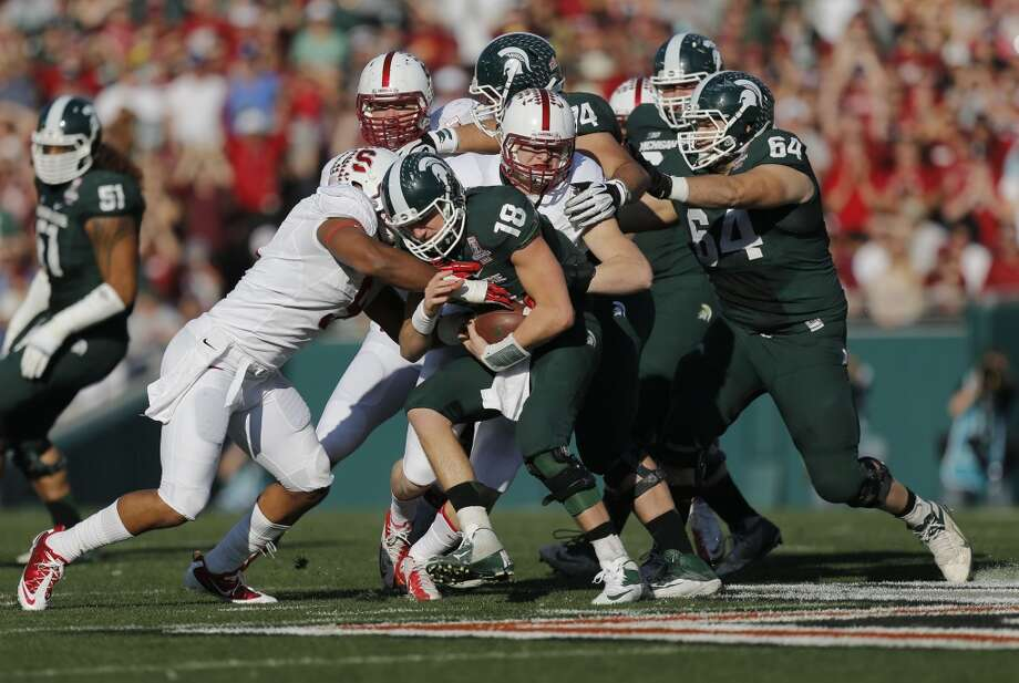 Stanford defenders James Vaughters (9) and Trent Murphy, (93) contain Michigan quarterback Connor Cook, (18) for a loss in  the first quarter, as the Stanford Cardinal and the Michigan State Spartans prepare to face off at the 100th Rose Bowl game in Pasadena, Ca. on Wednesday Jan. 1, 2014. Photo: Michael Macor, The Chronicle