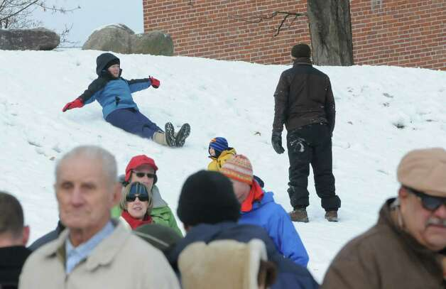A woman slides down a small hill at Shepard Park Beach behind a crowd of people watching the annual Lake George Polar Plunge on Wednesday, Jan. 1, 2014 in Lake George, N.Y. (Lori Van Buren / Times Union) Photo: Lori Van Buren