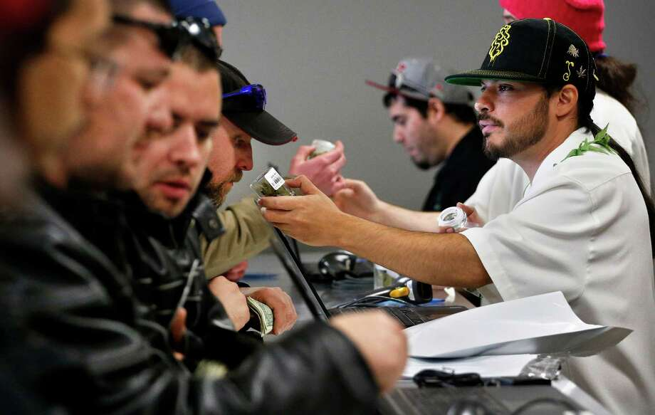 Employee David Marlow, right, helps a customer, who smells a strain of marijuana before buying it, at the crowded sales counter inside the Medicine Man retail store in Denver. Photo: Brennan Linsley, STF / AP