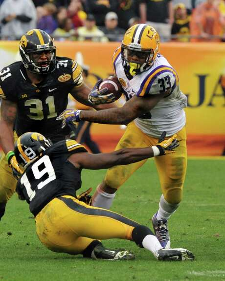 LSU's Jeremy Hill brushes aside Iowa's B.J. Lowery (19) while picking up a portion of his 216 yards. Photo: Al Messerschmidt, Stringer / 2014 Getty Images