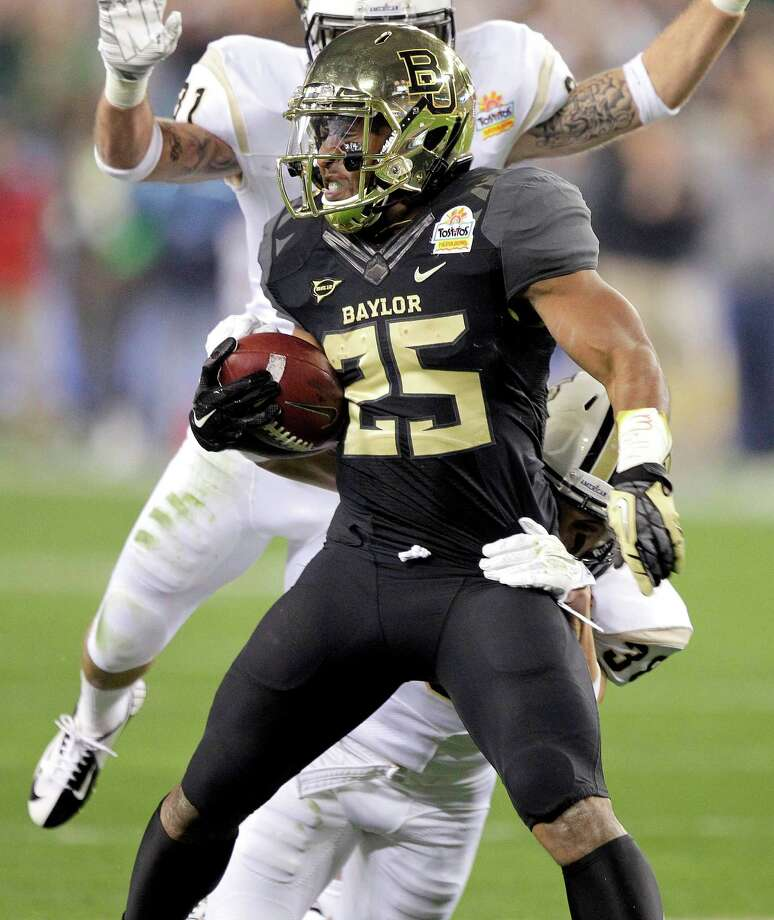 Baylor running back Lache Seastrunk (25) is brought down by Central Florida defensive back Jordan Ozerities, rear, and Sean Maag, top. during the first half of the Fiesta Bowl NCAA college football game, Wednesday, Jan. 1, 2014, in Glendale, Ariz. (AP Photo/Rick Scuteri) Photo: Rick Scuteri, Associated Press / FR157181 AP