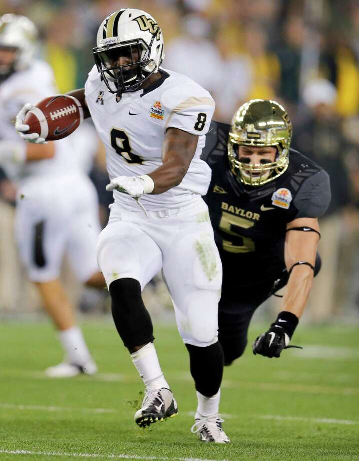 Central Florida running back Storm Johnson (8) breaks free from Baylor linebacker Eddie Lackey (5) for a touchdown during the first half of the Fiesta Bowl NCAA college football game, Wednesday, Jan. 1, 2014, in Glendale, Ariz. (AP Photo/Matt York) Photo: Matt York, Associated Press / AP