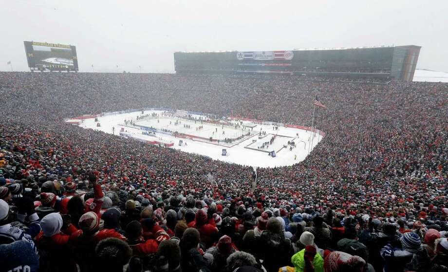Hockey fans stand during the national anthems before the Winter Classic outdoor NHL hockey game between of the Toronto Maple Leafs and the Detroit Red Wings at Michigan Stadium in Ann Arbor, Mich., Wednesday, Jan. 1, 2014. (AP Photo/Carlos Osorio) ORG XMIT: MICO101 Photo: Carlos Osorio / AP