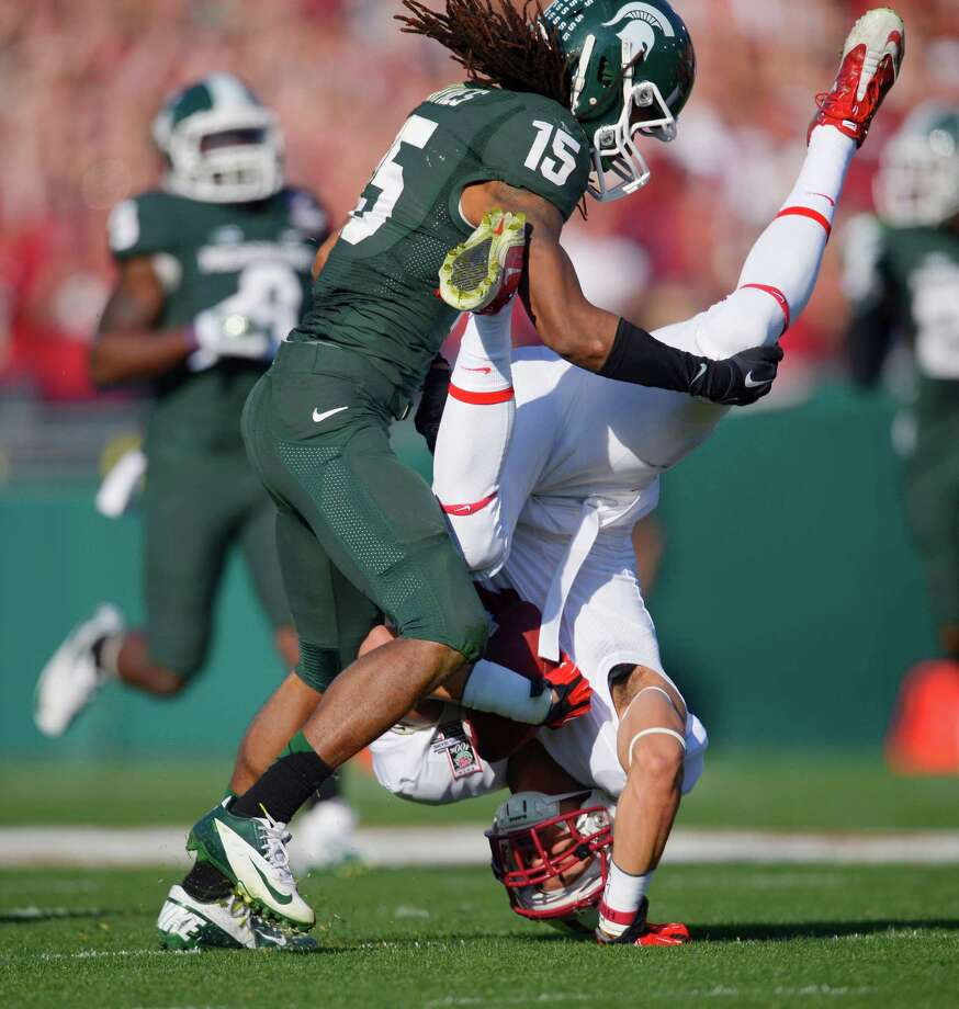 Stanford wide receiver Michael Rector, right, is flipped upside down by Michigan State cornerback Trae Waynes during the first half of the Rose Bowl NCAA college football game Wednesday, Jan. 1, 2014, in Pasadena, Calif. (AP Photo/Mark J. Terrill) ORG XMIT: PRB113 Photo: Mark J. Terrill / AP