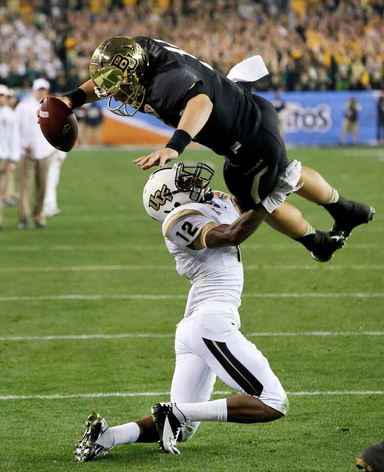 Baylor quarterback Bryce Petty  leaps over Central Florida defensive back Jacoby Glenn (12) for a touchdown during the first half of the Fiesta Bowl NCAA college football game, Wednesday, Jan. 1, 2014, in Glendale, Ariz. (AP Photo/Ross D. Franklin) Photo: Ross D. Franklin, Associated Press / AP