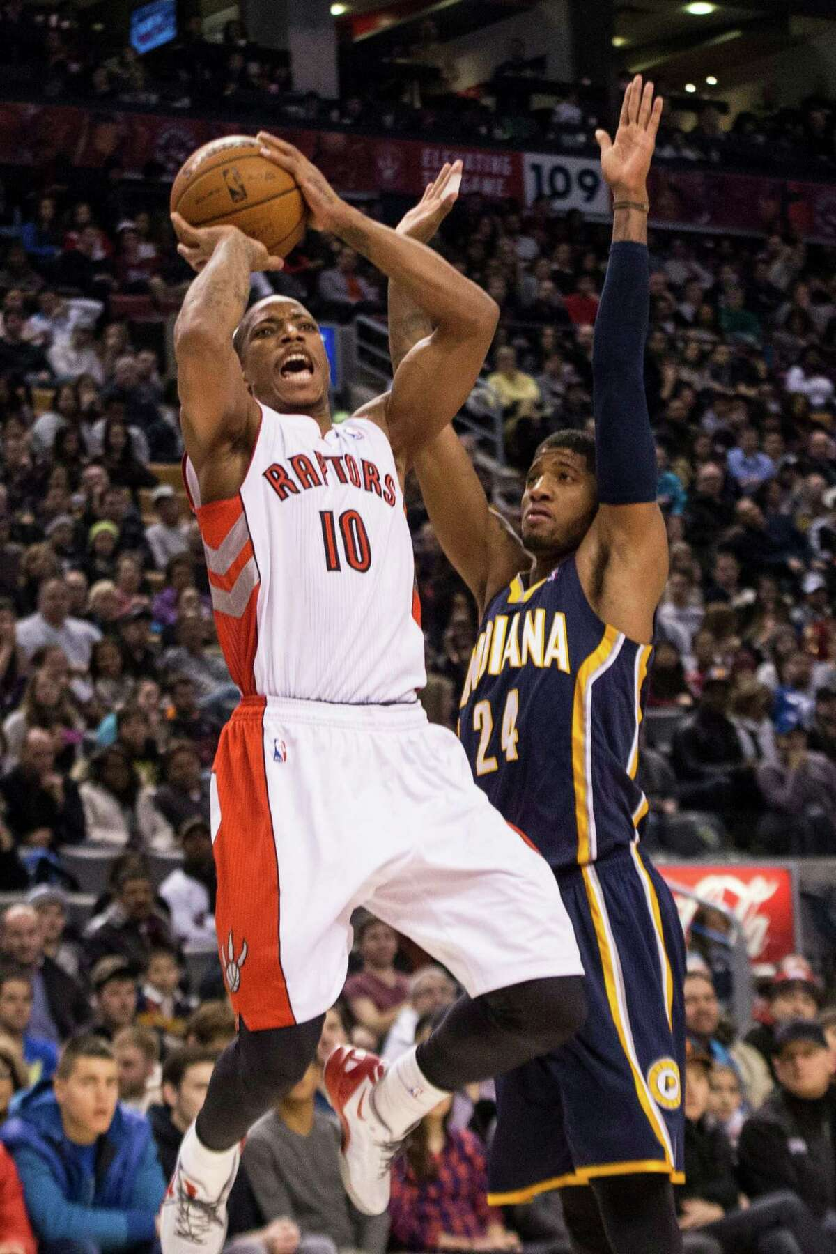 Toronto Raptors' DeMar DeRozan, left, shoots on Indiana Pacers' Paul George during the first half of an NBA basketball game in Toronto on Wednesday, Jan. 1, 2014. (AP Photo/The Canadian Press, Chris Young) ORG XMIT: CHY103