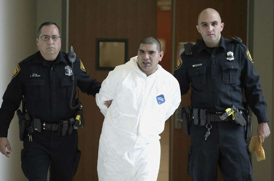 Police take suspect Eliseo Rosendo Altamirano to the magistrate's office after a man he had been with at a New Year's Eve party was beaten to death with a sledgehammer. Photo: Kin Man Hui / San Antonio Express-News / ©2013 San Antonio Express-News