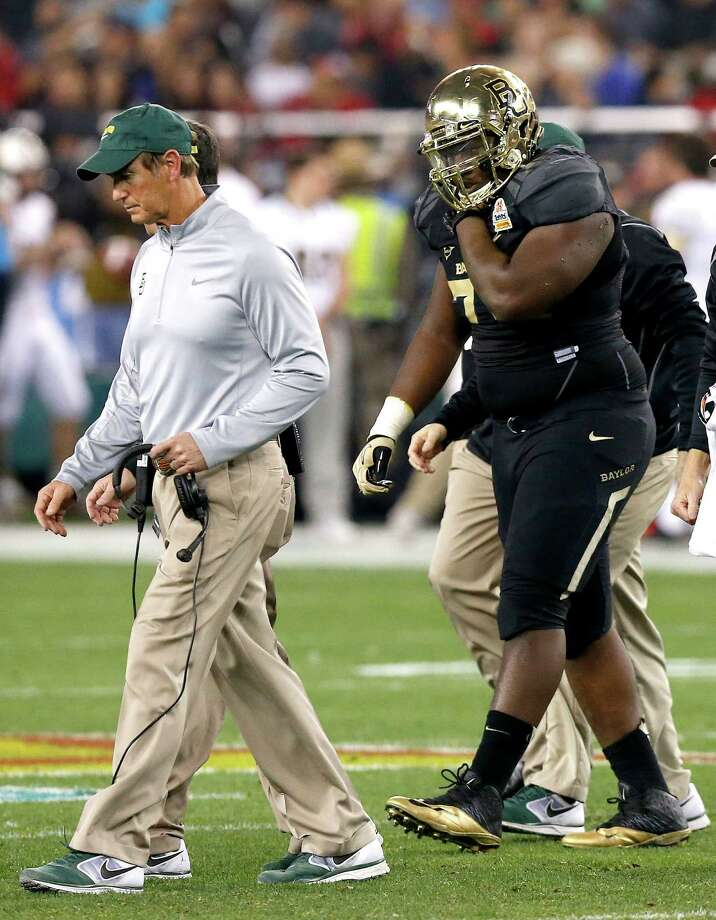 Baylor's Andrew Billings, right, leaves the field holding his right shoulder as coach Art Briles, left, walks off with him during the first half of the Fiesta Bowl NCAA college football game against Central Florida on Wednesday, Jan. 1, 2014, in Glendale, Ariz. (AP Photo/Ross D. Franklin) Photo: Ross D. Franklin, Associated Press / AP