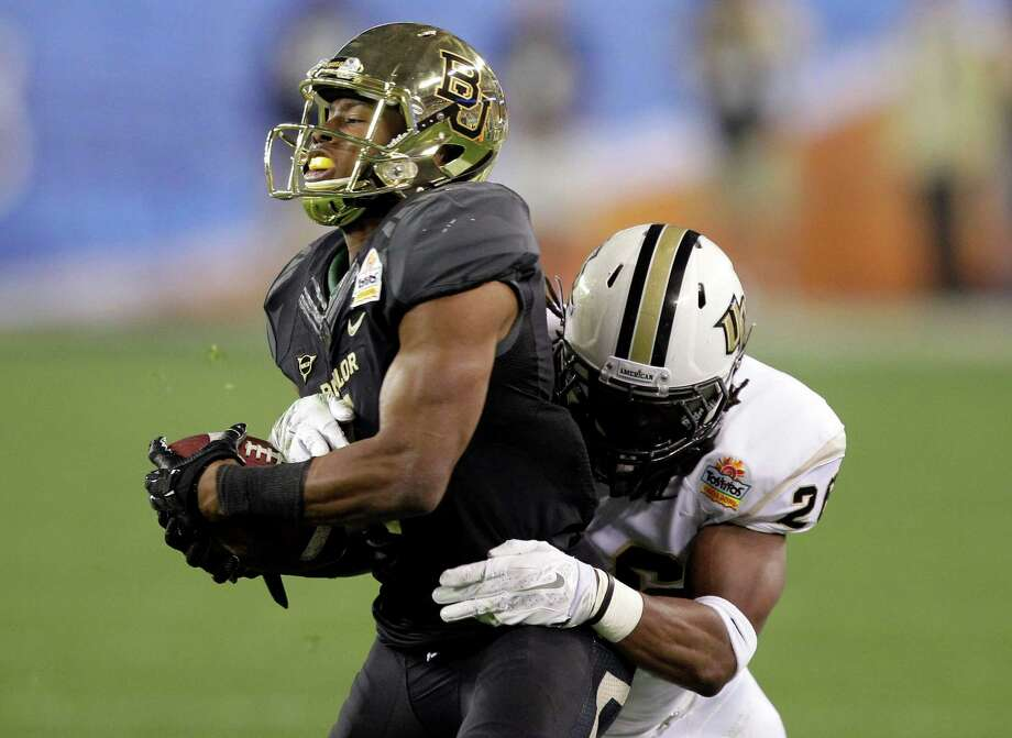 Baylor wide receiver Corey Coleman, left, is tackled by Central Florida defensive back Clayton Geathers during the first half of the Fiesta Bowl NCAA college football game, Wednesday, Jan. 1, 2014, in Glendale, Ariz.  (AP Photo/Rick Scuteri) Photo: Rick Scuteri, Associated Press / FR157181 AP