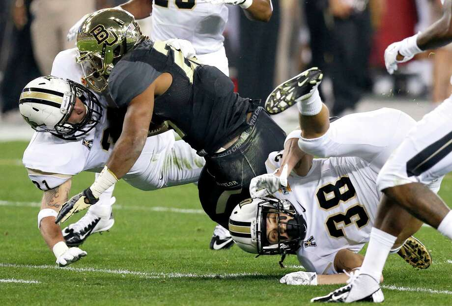 Baylor running back Lache Seastrunk, center, is tackled by Central Florida defensive back Sean Maag, left, and Jordan Ozerities during the first half of the Fiesta Bowl NCAA college football game, Wednesday, Jan. 1, 2014, in Glendale, Ariz.  (AP Photo/Ross D. Franklin) Photo: Ross D. Franklin, Associated Press / AP