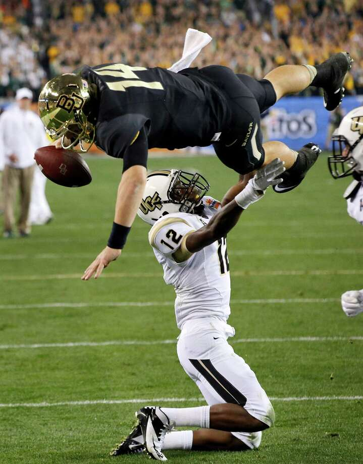 Baylor quarterback Bryce Petty  leaps over Central Florida defensive back Jacoby Glenn (12) for the touchdown during the first half of the Fiesta Bowl NCAA college football game, Wednesday, Jan. 1, 2014, in Glendale, Ariz.  (AP Photo/Ross D. Franklin) Photo: Ross D. Franklin, Associated Press / AP