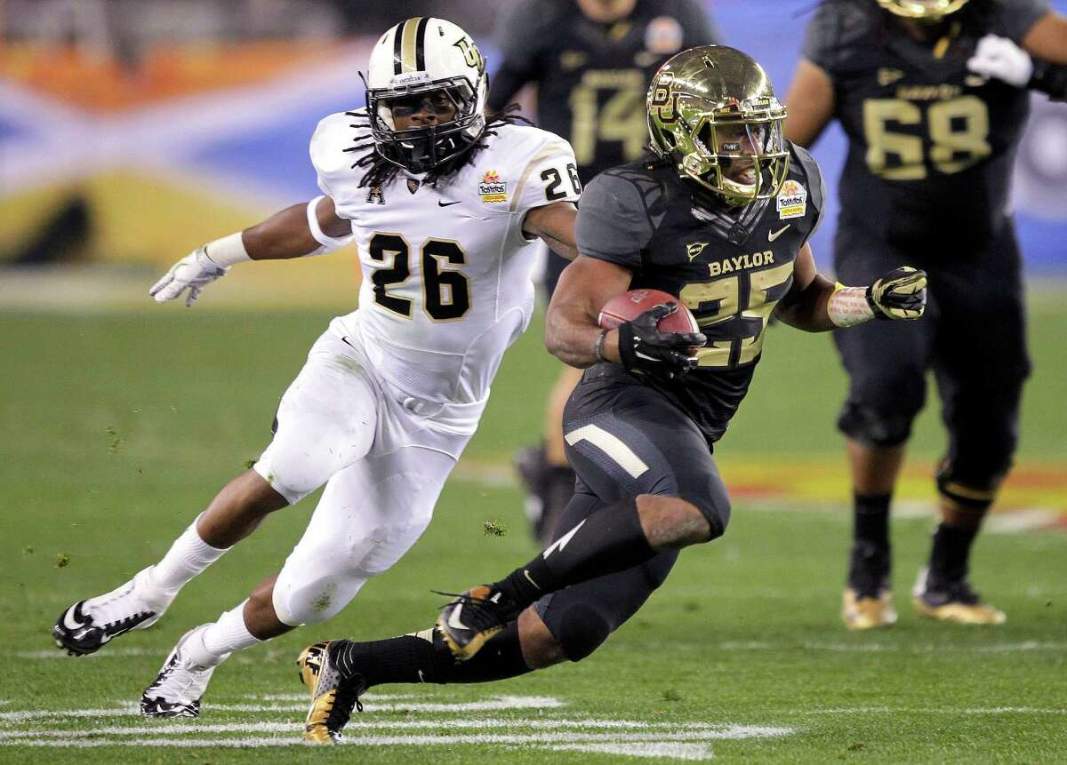 Baylor's Lache Seastrunk, right, makes a cut to try to elude Central Florida's Clayton Geathers.
