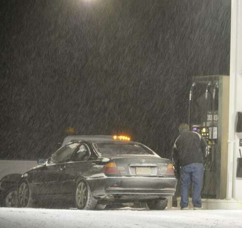 Snow falls in Malta as a man pumps gas into his car. Meteorologists predict up to a foot of snow could fall on the Capital Region before the storm ends Friday morning. (Skip Dickstein / Times Union)