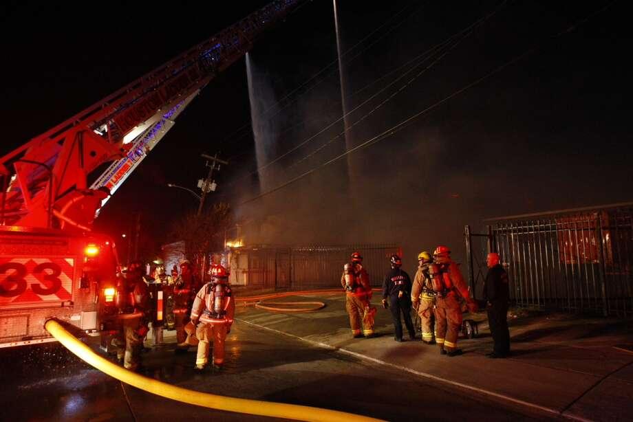Firefighters battle a blaze on Peerless near Dixie early Thursday morning, Jan. 2, 2014. Photo: Cody Duty, Houston Chronicle