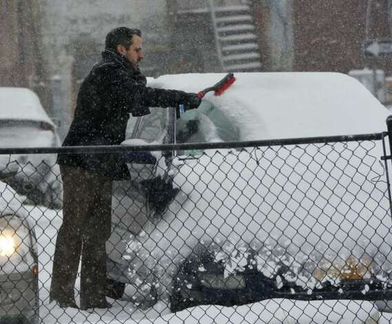Michael Jones brushes snow from his car in Albany on Thursday. The region was in the midst of a winter snow storm that was expected to drop up to a foot of snow by Friday morning. (Skip Dickstein / Times Union)