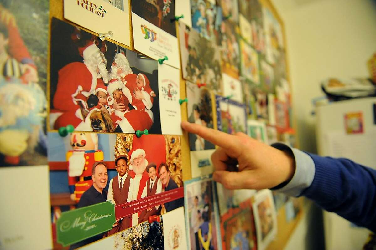 Kevin Fisher-Paulson points to Christmas cards that he and his husband Brian Fisher-Paulson have taken over the years.