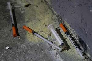 Hypodermic needles are left behind for a DPW downtown alley crew to clean up after a group of homeless men were ordered to move from Austin Street in San Francisco, Calif. on Thursday, Dec. 12, 2013.