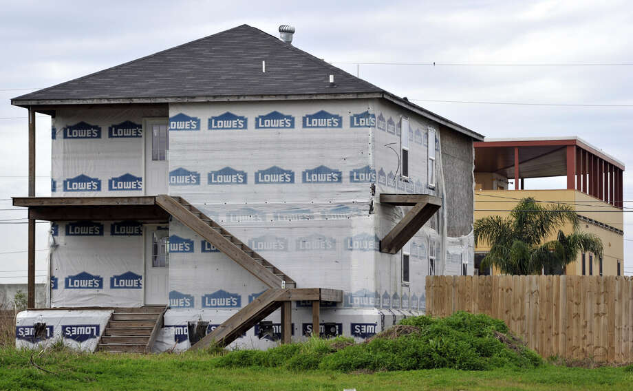 A vacant house sits in front  of One of the modular houses built by the Brad Pitt's Make It Right Foundation in the Lower Ninth Ward of New Orleans on February 5, 2013. Pitt rasied  $30 million for the project that consists of hurricane-proof homes. This area suffered the worst damage from Hurricane Katrina that occured in 2005 after multiple breaches in the levees of at least four canals. As of March 2009, hundreds of houses have been rebuilt, and dozens of new homes have been constructed. Photo: TIMOTHY A. CLARY, AFP/Getty Images / 2013 AFP