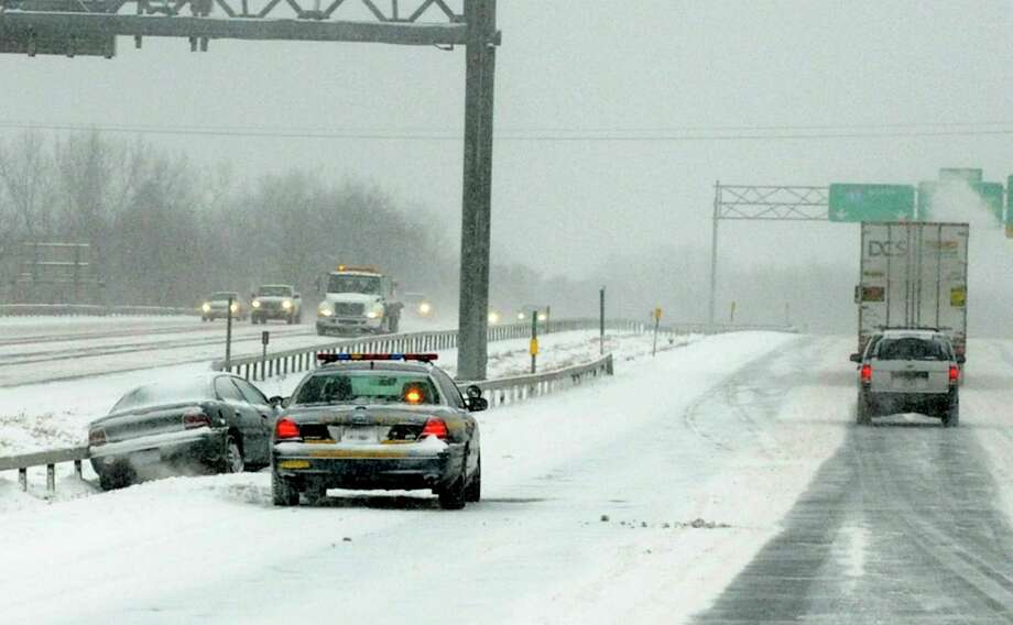 A state trooper is seen assisting a driver whose car slipped off I-87 northbound during a snow storm on Thursday, Jan. 2, 2014 in Colonie, N.Y. (Lori Van Buren / Times Union) Photo: Lori Van Buren / 00025207A