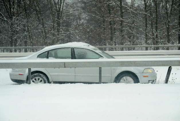 A car is stuck against the guardrail facing north on the southbound side of I-87 during a snow storm on Thursday, Jan. 2, 2014 in Colonie, N.Y. (Lori Van Buren / Times Union) Photo: Lori Van Buren / 00025207A