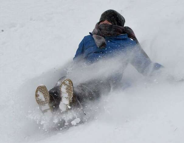 Jonathan Zaloga, 6, of Colonie enjoys the powder as he slides down a hill in Colonie during Thursday's snowstorm. (Skip Dickstein / Times Union)