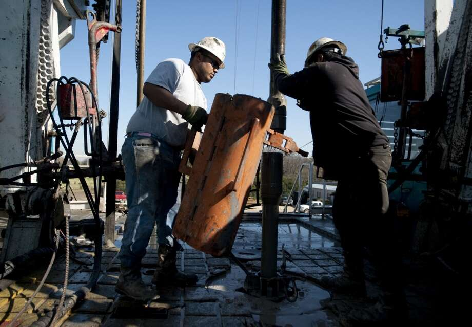 Toronto-based Trinidad Drilling Ltd. floorhands Julio Serrato, left, and Jaime Gonzalez work on the first drilling of the Reveille 1H Chesapeake Energy Corp. natural gas site in Fort Worth, Texas, U.S., on Monday, Nov. 23, 2009. Photo: Matt Nager, Bloomberg