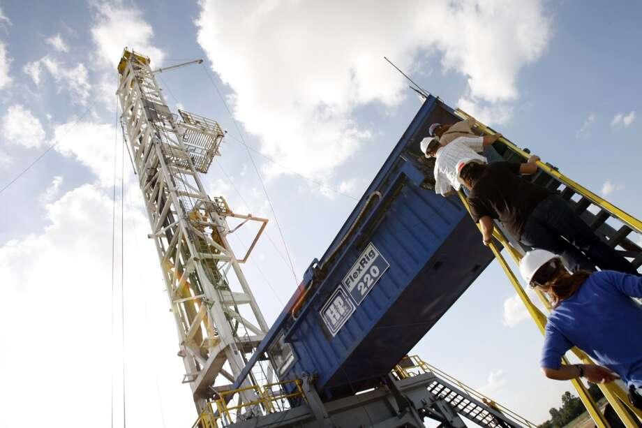 A Devon Energy flex-drilling rig reaches the blue sky Tuesday, June 10, 2008, near Denton. Photo: Kevin Fujii, Houston Chronicle