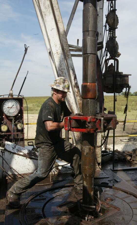 Levi Denno, oil rig worker, moves a section of drill pipe into position on the deck of the Napp Unit's  #1H rig in the  Barnett Shale oil field in Johnson County ,TX. Photo: Andrew Innerarity, Houston Chronicle