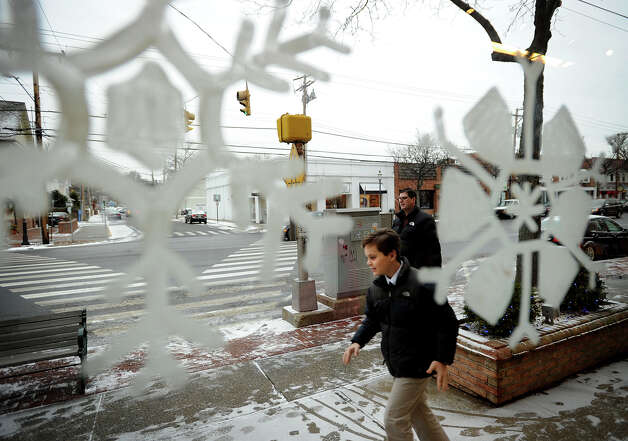 Pedestrians walk past the snowflake decorated windows of the Fairfield University Bookstore on the Post Road in downtown Fairfield, Conn. on Thursday, January 2, 2014. Photo: Brian A. Pounds / Connecticut Post