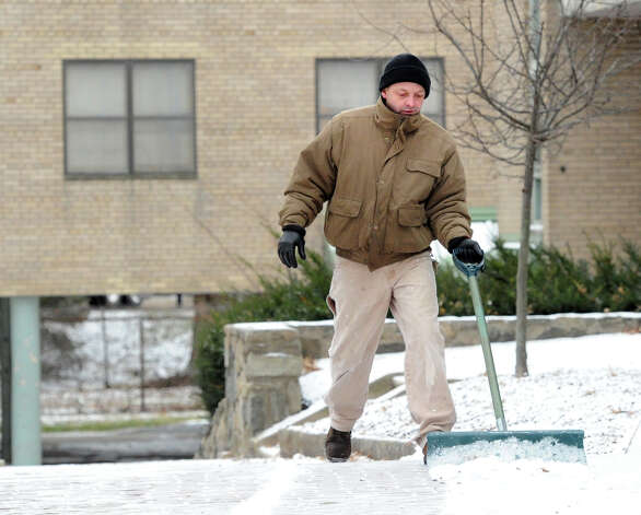 Town of Greenwich worker Jose Alicea clears snow from a courtyard at the Armstrong Court Housing Complex in Greenwich, Thursday, Jan. 2, 2014. Photo: Bob Luckey / Greenwich Time