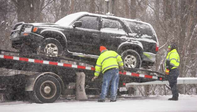 An SUV is loaded onto a flatbed after an accident in the north bound lanes of the Northway Thursday morning Jan. 2, 2014, in Colonie, NY.  (John Carl D'Annibale / Times Union) Photo: John Carl D'Annibale / 00025207A