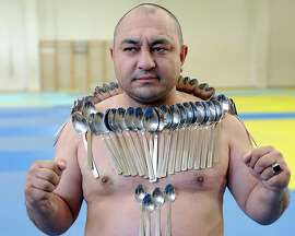 """Etibar Elchiyev poses with 53 metal spoons magnetized to his body during an attempt to break his own Guinness World Record for """"Most spoons on a human body"""" in Tbilisi on December 28, 2013."""