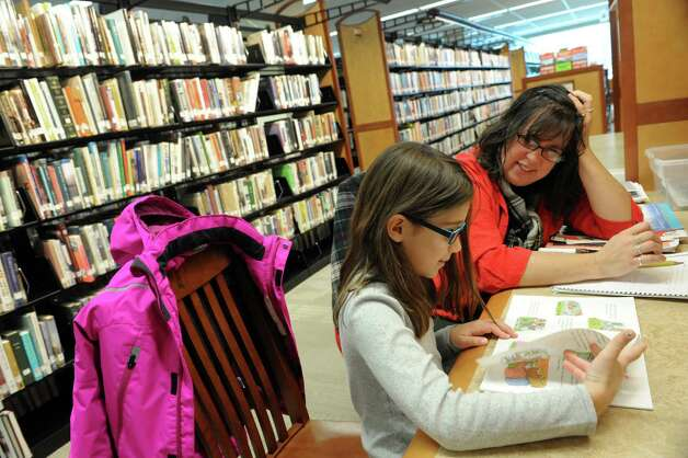 Nine-year-old Contessa Amedore works with her reading teacher Heidi Gerstenberger in the warmth of the Clifton Park-Halfmoon Public Library Thursday, Jan. 2, 2013, in Clifton Park, N.Y. (Michael P. Farrell/Times Union) Photo: Michael P. Farrell / 00025207A
