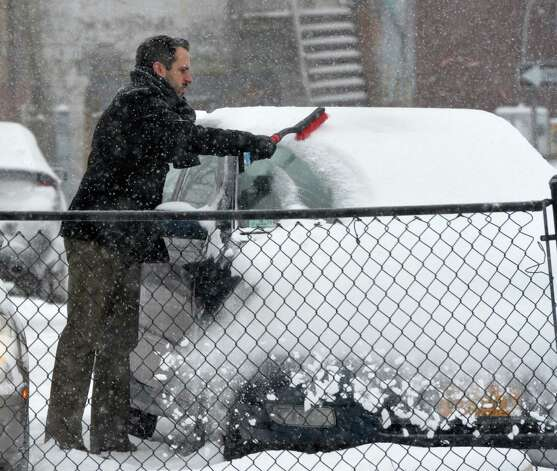 Michael Jones removes snow from his car Thursday morning, Jan. 2, 2013, on Washington Avenue in Albany, N.Y. (Skip Dickstein / Times Union) Photo: SKIP DICKSTEIN