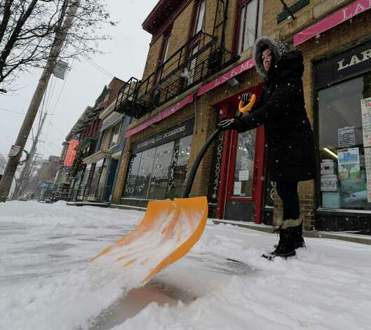 Tiffany Barkevick removes snow from the front of Lark Street Flower Market Thursday morning Jan. 2, 2013 during a snow storm that has socked in the Albany, N.Y.  area.    (Skip Dickstein / Times Union) Photo: SKIP DICKSTEIN