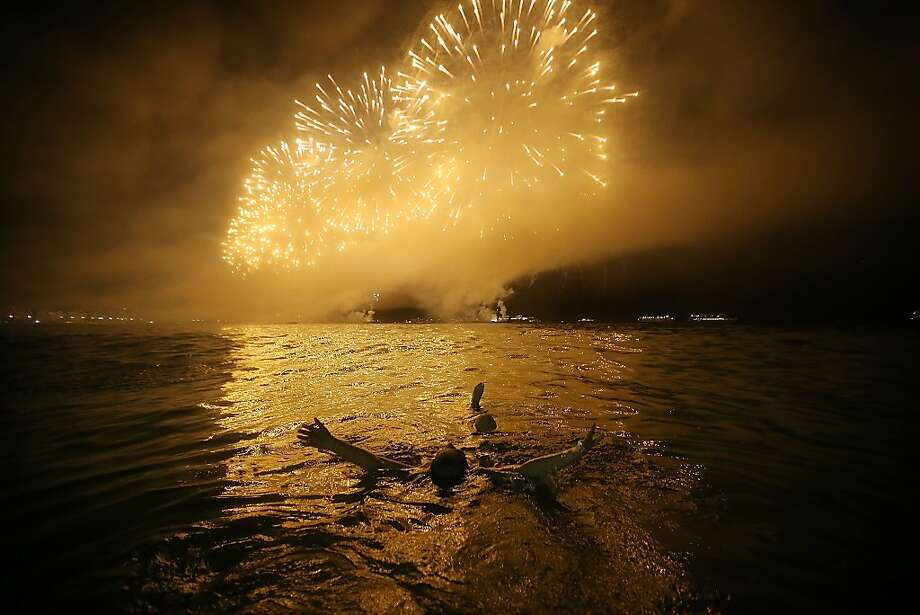 Enjoying the show:A Brazilian relaxes in the warm waters of Copacabana Beach as fireworks explode minutes after midnight Jan. 1 in Rio de Janeiro. Photo: Mario Tama, Getty Images
