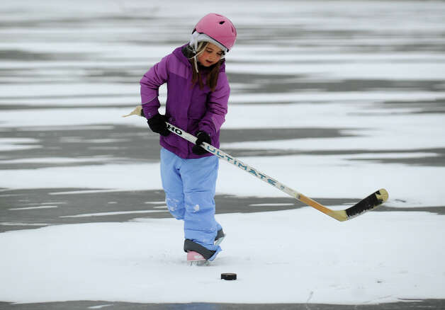 Alexandra Mazarelli, 7, of Easton, tries out her father Stephen's hockey stick during an afternoon of skating on the Samp Mortar Reservoir in Fairfield, Conn. on Thursday, January 2, 2014. Photo: Brian A. Pounds / Connecticut Post