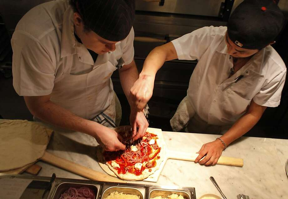 Above: Vincent Munich, left and Carlos Uz prepare a pizza that's the mainstay of the menu at Pizzeria Delifina on Burlingame Avenue (left). Photo: Lacy Atkins, The Chronicle