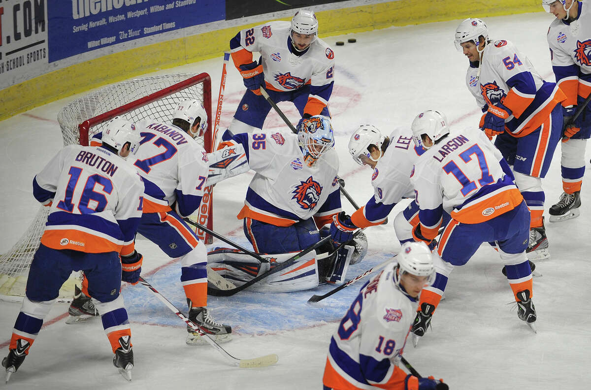 Sound Tigers goalie Kenny Reiter is surrounded as his teammates try to knock the puck home during pre-game warmups at the Webster Bank Arena in Bridgeport, Conn. on Sunday, November 24, 2013.