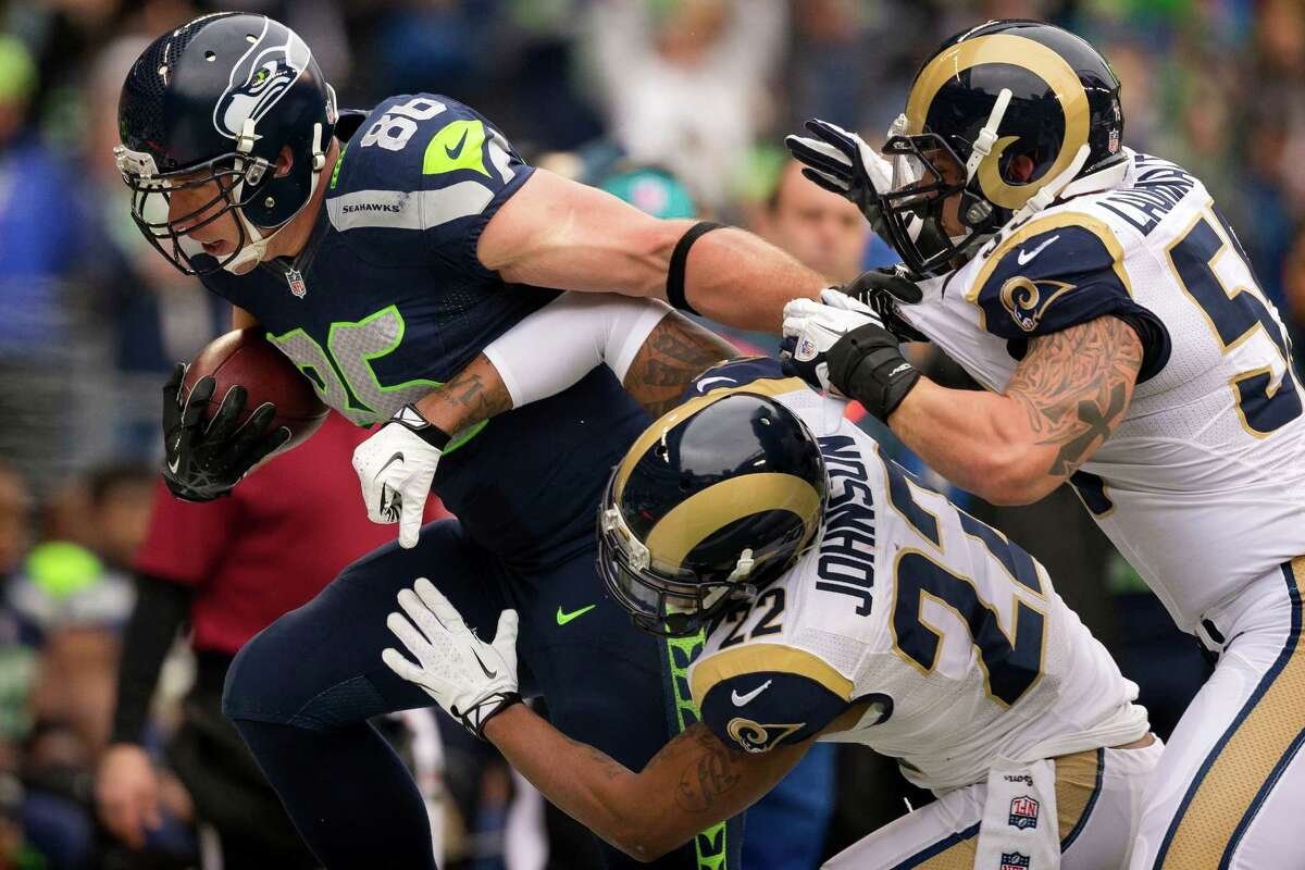 Seahawk Zach Miller, left, is swarmed by Rams' defense during the first half of the final regular season game Sunday, Dec. 29, 2013, at CenturyLink Field in Seattle. The Seahawks led the Rams 13-0 at the half.