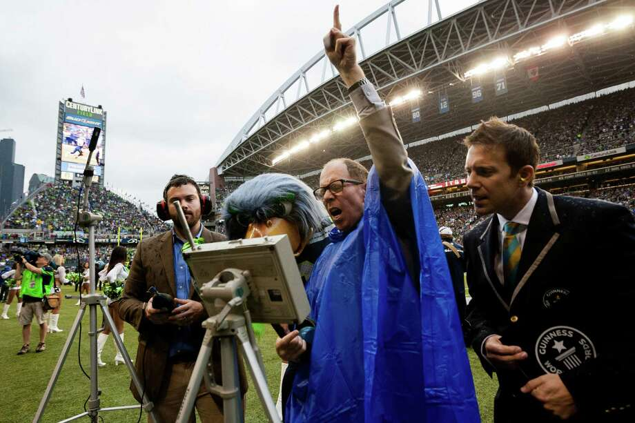 Sound engineer Bill Stewart, in blue, tries to hype up the crowd in an effort to tip the scales on the new decibel level of the stadium during the first quarter of the home opener of the season Sunday, September 15, 2013, at CenturyLink Field in Seattle. The record was reset at 136.6 decibels. Photo: JORDAN STEAD, SEATTLEPI.COM / SEATTLEPI.COM