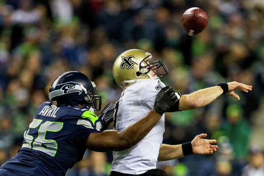 Seahawk Cliff Avril, left, knocks the ball free from the hand of the New Orleans Saints' quarterback, Drew Brees, right, during the first half of game Monday, Dec. 2, 2013, at CenturyLink Field in Seattle. The Seahawks led the Saints 27-7 at the end of the first half.