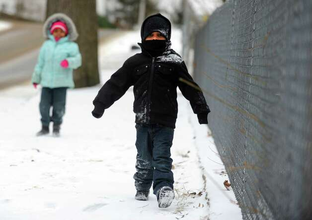 Three-year-old Charles Silva Jr. and Nevaeh James, 4, of Ansonia, walk down a snow covered street Thursday, Jan. 2, 2013 in Ansonia, Conn. Photo: Autumn Driscoll / Connecticut Post