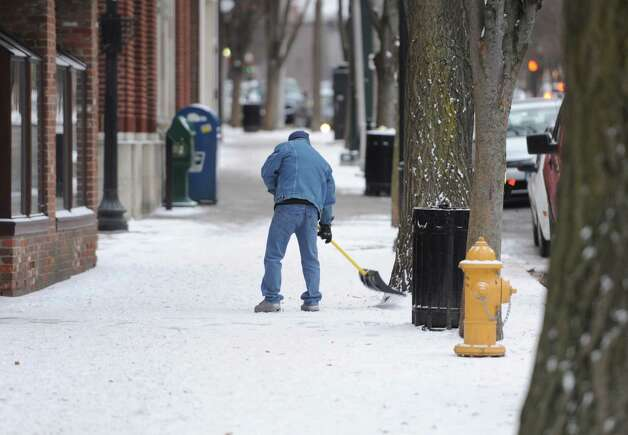 A man shovels snow from the sidewalk along Main Street in Danbury, Conn. on Thursday, Jan. 2, 2014. Photo: Tyler Sizemore / The News-Times