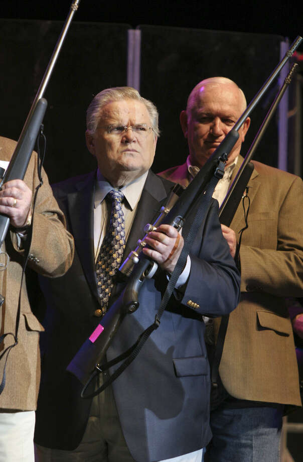 A stern-looking the Rev. John Hagee holds a rifle he presented in 2007 to a  wounded Iraq War veteran. Hagee exhorts the country to restore God to government and schools. He invites those who resist Christ in Christmas to leave the country. Photo: Express-News File Photo / SAN ANTONIO EXPRESS-NEWS