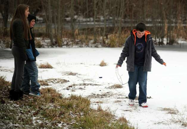 Nick Nielsen, 10, tests the edge of Pine Rock Park Pond as friends Mark Savo, 11, and Haley Constantino, 14, look on Thursday, Jan. 2, 2014 in Shelton, Conn. Photo: Autumn Driscoll / Connecticut Post
